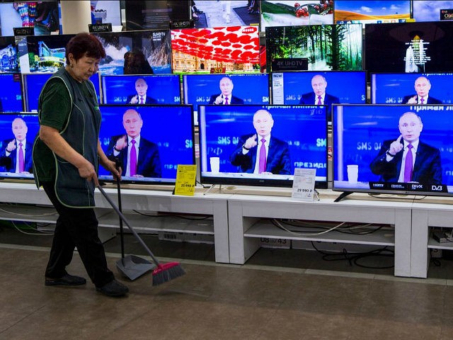 A cleaner walks past TV sets showing Russian President Vladimir Putin during his annual live call-in show in a shop in Moscow, Russia, Thursday, June 15, 2017. Putin had his annual live call-in show, a TV marathon lasting for hours in which he is widely expected to declare his intention …