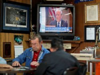 A newscast showing President Donald Trump plays on an old television set as customers play cards in the Frosty Freeze restaurant in Sandy Hook, Ky., Thursday, Dec. 14, 2017. Many families here can trace their ancestry back generations on the same land. Almost everyone is white, and almost everyone is …