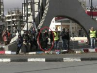A Palestinian attacker, hiding among journalists, before he stabbed a Border Police officer in the West Bank city of Ramallah on December 15, 2017. (Israel Police)