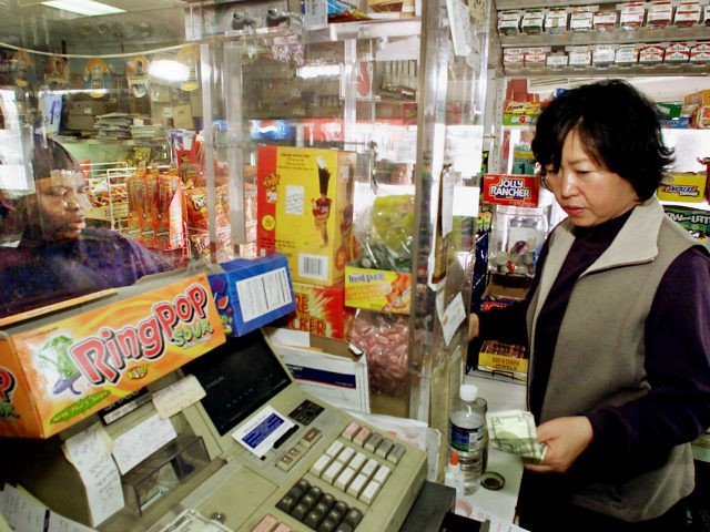 Store owner April Kim makes a sale to an African-American customer from inside a protective glass cage at the store she owns in South Central Los Angeles Tuesday, April, 9, 2002. Relations between Korean-American store owners and their black and Hispanic customers have come a long way in the 10 …
