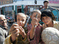 Young Uighur boys display their switch-blades while posing with a girl holding a soccer ball in Hotan, located in China's far west Xinjiang Region, in October 2006. (Credit: FREDERIC J. BROWN/AFP/Getty Image) [-]