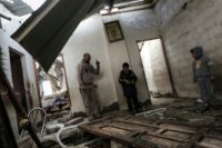 A Palestinian man and children check their house that was damaged in an Israeli airstrike on a nearby Hamas base, in Khan Yunis town in the southern Gaza Strip in December 13, 2017