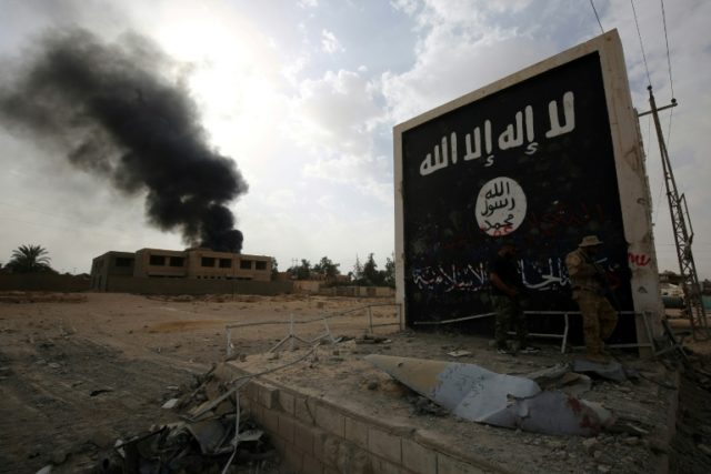 Iraqi fighters stand next to a wall bearing the Islamic State group flag in western Anbar province