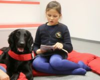 Eight-year-old Urte reads to therapy dog Mona at Lithuania's national library in Vilnius