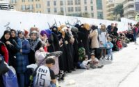 "Syrian refugees queue to receive aid in Beirut's Martyrs Square on November 26, 2017, as part of the ""Dafa"" campaign aimed at helping Syrian refugees and Lebanese families in need"