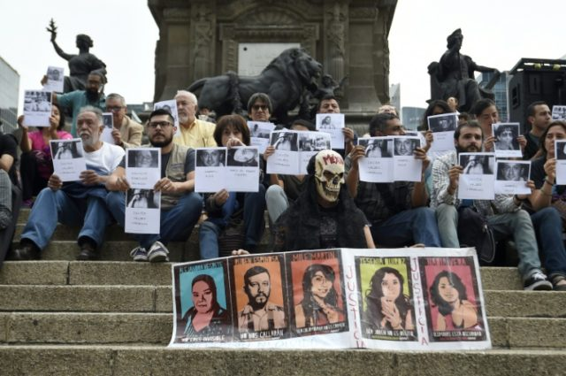 Journalists protest against violence during a commemoration of the 30th anniversary of the murder of Mexican journalist Manuel Buendia at the Angel de la Independencia monument in Mexico City