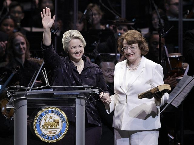 Houston Mayor Annise Parker, left, waves as her partner, Kathy Hubbard, right, holds the Bible during a public inauguration ceremony Monday, Jan. 4, 2010 in Houston. Houston is the largest U.S. city to elect an openly gay mayor. (AP Photo/David J. Phillip)