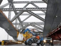 FILE - In this Nov. 15, 2016, file photo, a worker lifts materials as construction continues on the new roadway deck of the Bayonne Bridge in Bayonne, N.J. Even as they maneuver for a share of the $1 trillion in spending President-elect Donald Trump promised to rebuild America's roads, bridges …