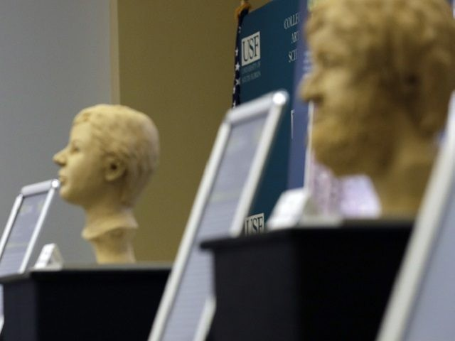 In this Oct. 21, 2016 photo, Dr. Erin Kimmerle, standing next to forensic sculptures of unidentified murder victims, speaks to a group of detectives, researchers, and prosecutors during a forensics conference in Tampa, Fla. Kimmerle is hoping her scientific research can help find identities of cold case victims. (AP Photo/Chris …