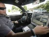 FILE- In this July 16, 2013, file photo, Officer Dennis Vafier, of the Alexandria Police Department, uses a laptop in his squad car to scan vehicle license plates during his patrols in Alexandria, Va. It would violate people's privacy to publicly release raw data collected by automated license plate readers …