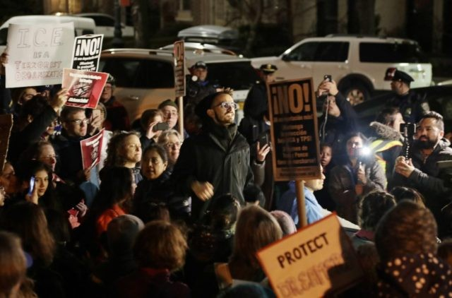 Protestors gather across the street from the home of Sen. Charles Shumer, D-N.Y Tuesday, Jan. 23, 2018, in New York. Schumer faced heated criticism from frustrated liberals and giddy Republicans who said he caved on Democrats' wish to protect young immigrants from deportation. (AP Photo/Frank Franklin II)