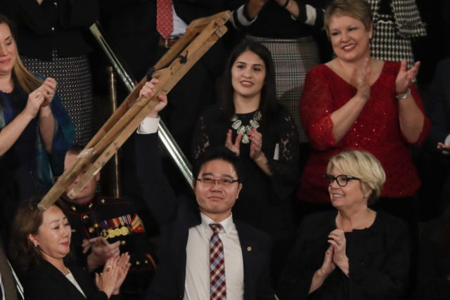 Ji Seong-ho holds up his crutches after his introduction by President Trump during the State of the Union address to a joint session of Congress on Capitol Hill in Washington, Tuesday, Jan. 30, 2018. (AP Photo/J. Scott Applewhite)