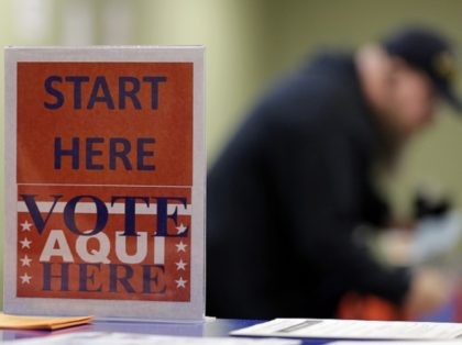 In this Wednesday, Feb. 26, 2014 photo, a voter prepares to cast his ballot at an early voting polling site, in Austin, Texas. In elections that begin next week, voters in 10 states will be required to present photo identification before casting ballots _ the first major test of voter …