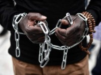 An African migrant with his hands chained, takes part in a march towards the offices of the European Union during a demonstration on December 2, 2017 in central Athens, protesting against the slavery of migrants in Libya and against the deals between the European Union (EU) and Turkey and between …