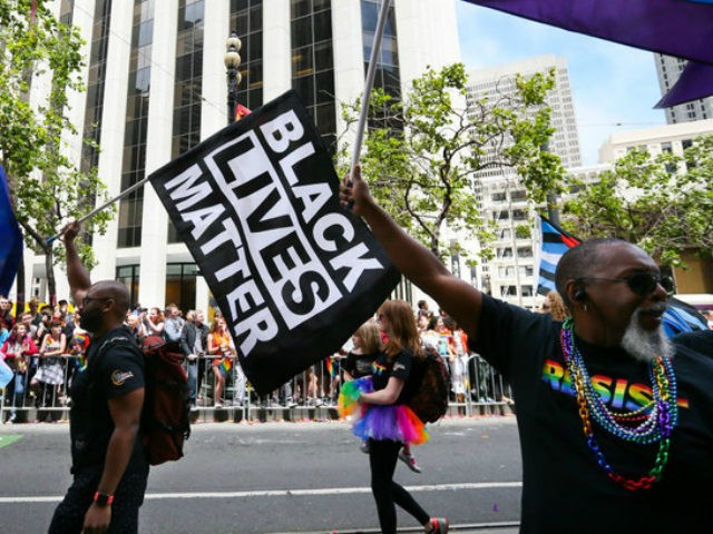 Men wave rainbow and 'black lives matter' flags while marching in the annual LGBTQI Pride Parade on Sunday, June 25, 2017 in San Francisco, California. The LGBT community descended on Market Street for the 47th annual Pride Parade. (Photo by Elijah Nouvelage/Getty Images)
