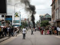 People look on as protesters burn tyres during a demonstration calling for the President of the Democratic Republic of the Congo to step down on January 21, 2018 in Kinshasa.