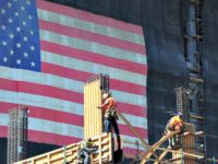 Construction workers work the construction of a new building partly covered with a large US flag on September 25, 2013 in Los Angeles, California, where the state's Governor Jerry Brown signed legislation that will raise the California minimum wage from $8 to $10 per hour by 2016. AFP PHOTO/Frederic J. …