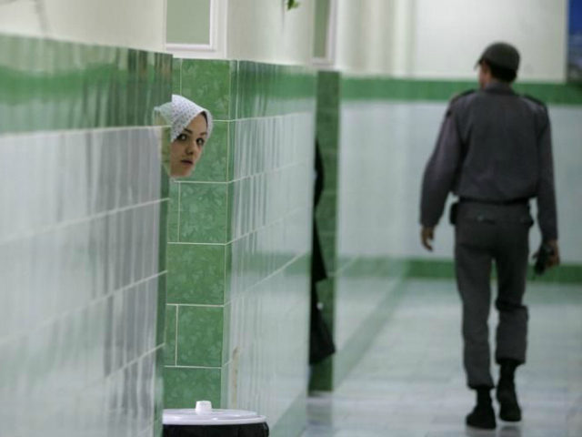 An Iranian inmate peers from behind a wall as a guard walks by at the female section of the infamous Evin jail, north of Tehran, 13 June 2006. AFP PHOTO/ATTA KENARE (Photo credit should read ATTA KENARE/AFP/Getty Images)