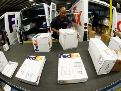 In this July 9, 2014, file photo, workers load packages into delivery trucks at the FedEx Express station in Nashville, Tenn. FedEx reports quarterly financial results on Wednesday, June 17, 2015. (AP Photo/Mark Humphrey)