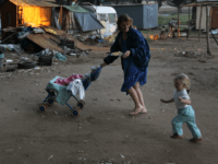 KRUGERSDORP, SOUTH AFRICA - JUNE 07: Chantell Lubbe carries a plate full of free food while walking with her children through a White South African squatter camp on June 7, 2010 in Krugersdorp, South Africa. The local municipality tried to evict the squatters from the land last year to make …