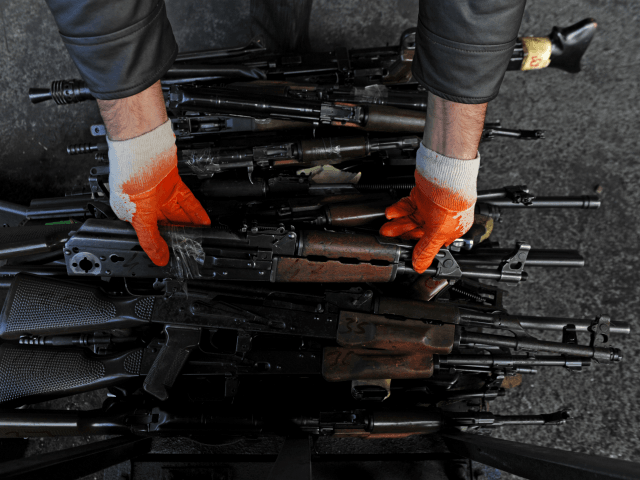 A Kosovar employee shows seized weapons before destroying them at a metal foundry near the village of Janjevo on October 10, 2013. Around 1,300 small arms and light weapons were seized during the investigation of different types of crime during the last three years. AFP PHOTO/ARMEND NIMANI (Photo credit should …