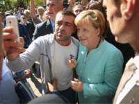 BERLIN, GERMANY - SEPTEMBER 10: German Chancellor Angela Merkel pauses for a selfie with a migrant after she visited the AWO Refugium Askanierring shelter for migrants on September 10, 2015 in Berlin, Germany. Merkel visited several facilities for migrants today, including an application center for asylum-seekers, a school with welcome …