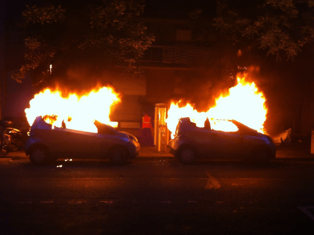 TOPSHOT - A photo taken on June 14, 2016 shows two Autolibs (the French electric car pick-up service) on fire in a street of Paris after been burnt by a group of hooded people. / AFP / Samantha DUBOIS (Photo credit should read SAMANTHA DUBOIS/AFP/Getty Images)