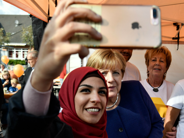 A syrian refugee (L) poses for a selfie photo with German Chancellor Angela Merkel (C) as she continued on the election campaign trail in Stralsund on September 16, 2017, a week before Germans head to the polls. / AFP PHOTO / John MACDOUGALL / ALTERNATIVE CROP (Photo credit should read …