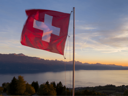 A Swiss flag is seen floating at sunset above Lake Geneva on October 5, 2017 from the Mont de Gourze in Riez, western Switzerland. / AFP PHOTO / Fabrice COFFRINI (Photo credit should read FABRICE COFFRINI/AFP/Getty Images)