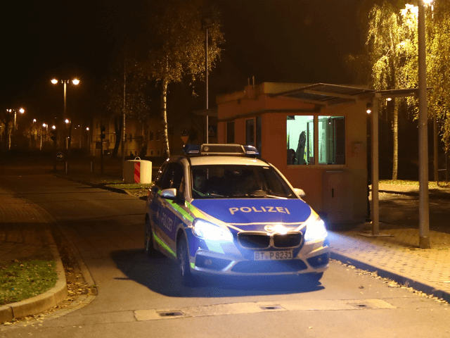 A police car leaves the grounds of a reception centre for asylum seekers in Bamberg, southern Germany, on early November 15, 2017. A man was killed and 14 residents of the home were injured as a fire broke out. The cause of the fire is yet unclear. / AFP PHOTO …