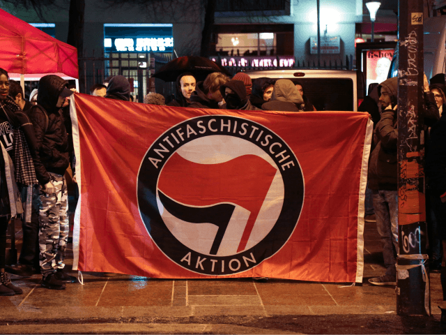 Activists hold a banner from the German anti-fascist network 'Antifaschistische Aktion' during a gathering in the Belleville district of Paris on January 17, 2018 to celebrate the French government's decision to scrap controversial plans for a new Atlantic coast airport. France scrapped controversial plans on January 17 for a new …