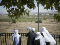 A Druze family, celebrating the Eid al-Adha holiday, look towards Syria's Quneitra province as they visit an observation point in the Israeli-controlled Golan Heights, Tuesday, Sept. 13, 2016. Israel is denying Syrian government claims that its forces shot down a warplane and a drone near the Israeli-controlled part of the …