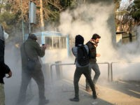 Iranian students run for cover from tear gas at the University of Tehran during a demonstration driven by anger over economic problems, in the capital Tehran on December 30, 2017. Students protested in a third day of demonstrations, videos on social media showed, but were outnumbered by counter-demonstrators. / AFP PHOTO / STR (Photo credit should read STR/AFP/Getty Images)