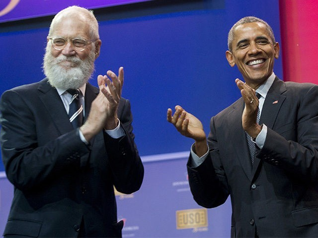 US President Barack Obama applauds alongside former talk show host David Letterman during a celebration of the 5th anniversary of Joining Forces and the 75th anniversary of the USO at Andrews Air Force Base in Maryland
