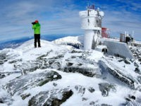 In this Tuesday, March 10, 2015 photo, Ryan Eyestone, 31, of Portland, Maine, makes a photographs near the weather instrument tower of the Mount Washington Observatory on the summit of Mount Washington in New Hampshire. (AP Photo/Robert F. Bukaty)