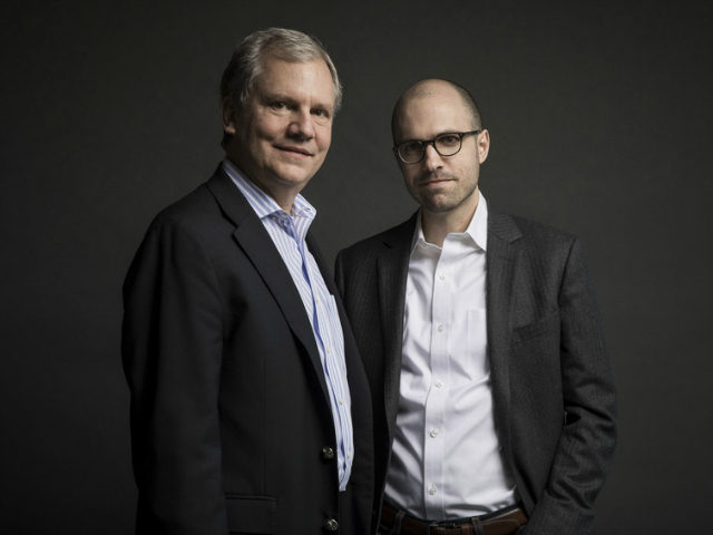 In this Dec. 13, 2017 photo, Arthur O. Sulzberger Jr., left, poses with his son, Arthur Gregg Sulzberger, on the 16th floor of the New York Times building in New York. The New York Times announced on Thursday, Dec. 14, 2017, that Arthur O. Sulzberger Jr., will step down as …