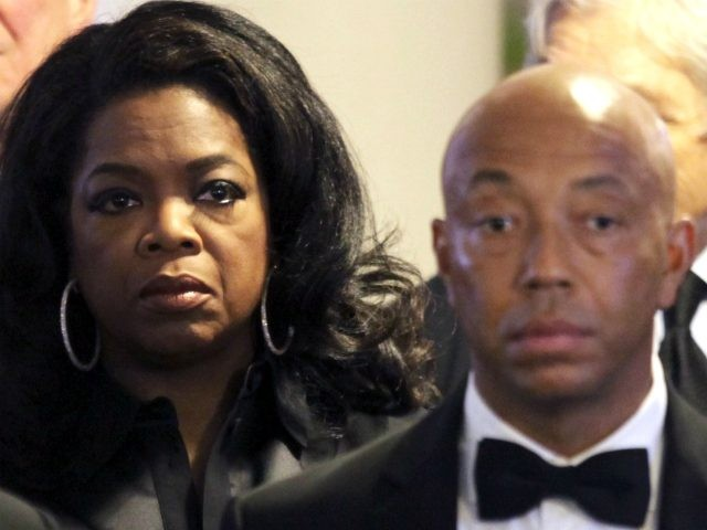 Oprah Winfrey, center, stands with Russell Simmons, right, and other mourners as the casket enters for the funeral of Eunice Kennedy Shriver at Saint Francis Xavier Roman Catholic Church in the Hyannis section of Barnstable, Mass., Friday, Aug. 14, 2009. Shriver, the sister of President John F. Kennedy and Massachusetts …