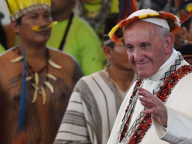 TOPSHOT - Pope Francis, wearing gifts, leaves after a meeting with representatives of indigenous communities of the Amazon basin from Peru, Brazil and Bolivia, in the Peruvian city of Puerto Maldonado, on January 19, 2018. Pope Francis sounded a stark warning about the future of the Amazon and its peoples …