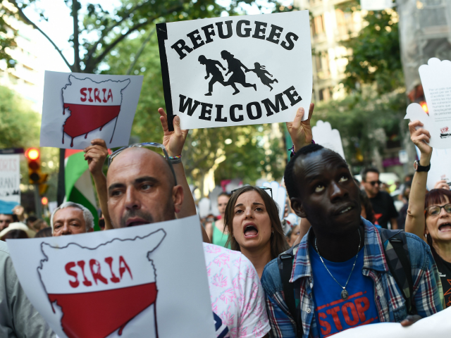 Protestors hold placards during a demonstration in a Barcelona on June 19, 2016 under the slogan, 'open borders, we welcome' in favour of rights for refugees and demanding that European authorities take action to secure safe passage routes for refugees. / AFP / JOSEP LAGO (Photo credit should read JOSEP …