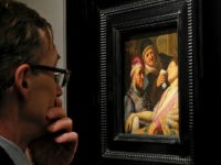 A visitor to the booth of Galerie Talabardon & Gautier at the TEFAF fine art fair looks at a newly discovered painting by Dutch master Rembrandt titled The Unconscious Patient (Sense of Smell) dated at around 1624-25, oil on panel 21.6x17.8 cm, in Maastricht, southern Netherlands, Thursday, March 10, 2016. …