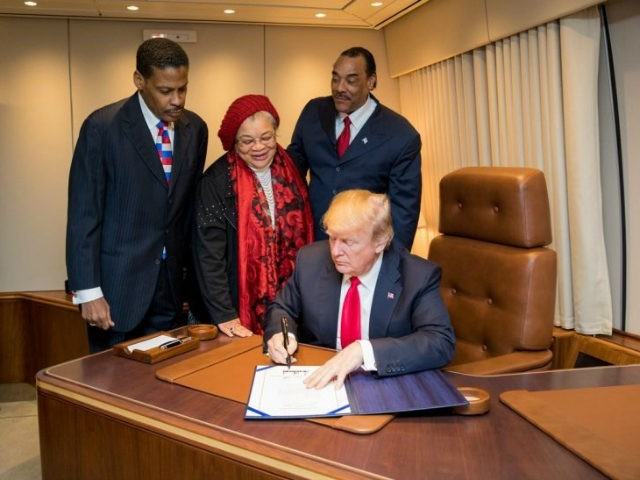 President Donald J. Trump, with Alveda King, center, niece of slain Civil Rights leader Dr. Martin Luther King Jr., and joined by Isaac Newton Farris Jr., left, nephew of Dr. King, and Bruce Levell of the National Diversity Coalition for Trump, right, signs the Martin Luther King Jr. National Historical Park Act, Monday, Jan. 8, 2018, aboard Air Force One, in Atlanta, Ga. (Official White House Photo by Shealah Craighead)
