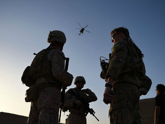 In this photograph taken on August 27, 2017 US Marines and Afghan Commandos stand together as an Afghan Air Force helicopter flies past during a combat training exercise at Shorab Military Camp in Lashkar Gah in Helmand province. Marines in Afghanistan's Helmand say Donald Trump's decision to keep boots on …
