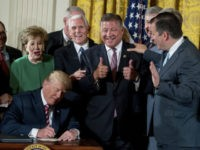 FILE - In this June 5, 2017, file photoRep. Bill Shuster, R-Pa., center, gives two thumbs up as he gets two autographs from President Donald Trump after Trump signs a decision memo and a letter to members of Congress outlining the principles of his plan to privatize the nation's air …