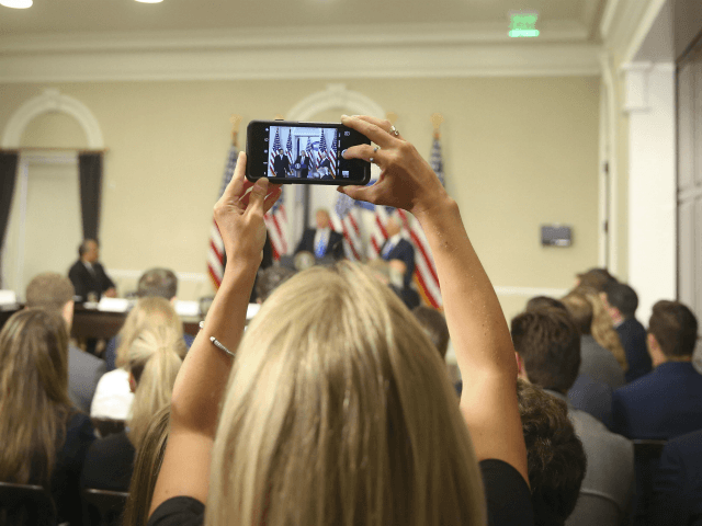 A White House staff members uses her cellphone to record President Donald Trump speaking at a meeting of the Presidential Advisory Commission on Election Integrity, Wednesday, July 19, 2017, in the Eisenhower Executive Office Building on the White House complex in Washington. (AP Photo/Pablo Martinez Monsivais)