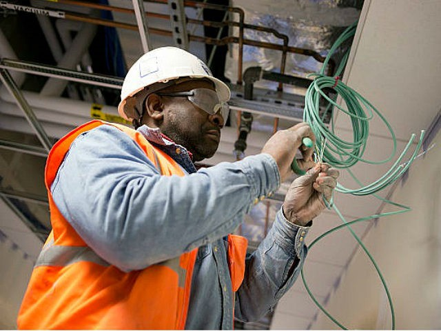 A contractor installs network cable at Skanska USA Building Inc.'s Inova Health System construction site in Lorton, Virginia, U.S., on Thursday, Jan. 3, 2013. Construction spending dipped 0.3 percent in November as gains in housing were not enough to offset declines in nonresidential and public construction, according to Census Bureau …