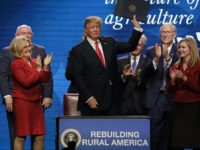 President Donald Trump acknowledges applause after signing an executive order at the American Farm Bureau Federation annual convention Monday, Jan. 8, 2018, in Nashville, Tenn. (AP Photo/Mark Humphrey)