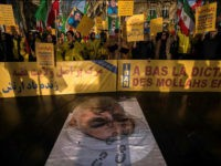 TOPSHOT - Protesters hold placards reading 'Support Iranians risen up against the religious dictatorship' as they stand behind a portrait of Iranian President Hassan Rouhani with shoe marks over it during a demonstration in support of the Iranian people amid a wave of protests spreading throughout Iran, on January 3, …