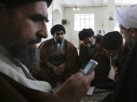 Shiite clerics talk, as one of them check his cell phone, at the Sadr seminary in the city of Isfahan some 234 miles (390 kilometers) south of the capital Tehran, Iran, Saturday, April 9, 2011. (AP Photo/Vahid Salemi)