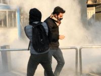 Iranian students run for cover from tear gas at the University of Tehran during a demonstration driven by anger over economic problems, in the capital Tehran on December 30, 2017. Students protested in a third day of demonstrations, videos on social media showed, but were outnumbered by counter-demonstrators. / AFP …