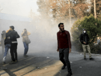 In this photo taken by an individual not employed by the Associated Press and obtained by the AP outside Iran, university students attend a protest inside Tehran University while a smoke grenade is thrown by anti-riot Iranian police, in Tehran, Iran, Saturday, Dec. 30, 2017. A wave of spontaneous protests …